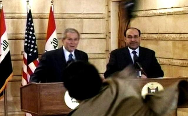 En journalist hiver en sko på President George W. Bush under en pressekonferanse med Iraks Statsminister Nouri al-Maliki Søndag, 14. Des., 2008, i Bagdad. Mannen kastet to sko på Bush, den ene etter den andre. Bush dukket unna begge skoene, og ble ikke truffet. Nå er journalisten fri igjen etter å ha vært fengslet og torturert.